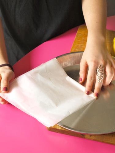 piegate un foglio di carta da forno in quattro e prendete le misure dal centro della teglia
